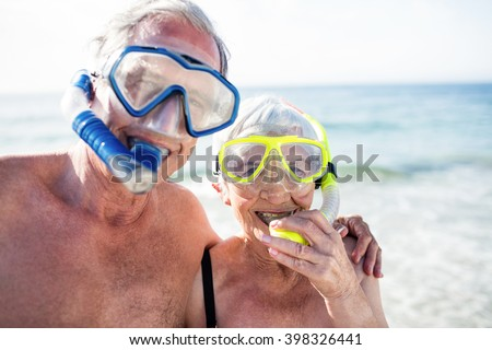 Portrait of happy senior couple with their diving mask at beach on a sunny day - stock photo