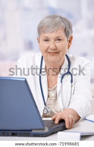 Portrait of happy senior doctor, sitting at desk, looking at camera, smiling.? - stock photo