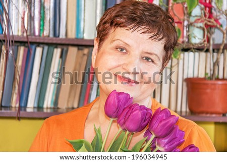 Portrait of happy senior elderly woman with bouquet (bunch) of tulips  at home in the birthday. Caucasian beautiful female in her 60s. Close up, indoor.   - stock photo