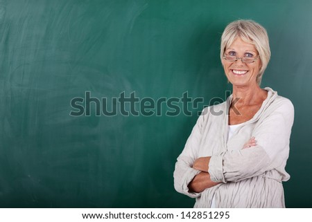 Portrait of happy senior female teacher with arms crossed standing against chalkboard - stock photo