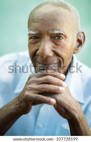 Portrait of happy senior hispanic man looking at camera and smiling - stock photo