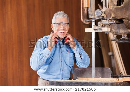 Portrait of happy senior male carpenter holding ear protectors by bandsaw in workshop - stock photo