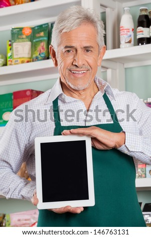 Portrait of happy senior male owner showing digital tablet in grocery store - stock photo
