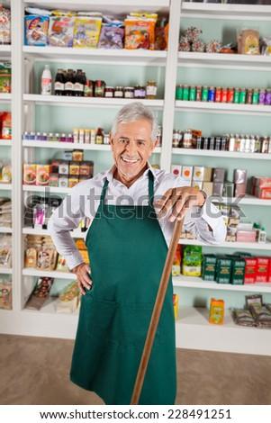 Portrait of happy senior male owner standing against shelves in supermarket - stock photo