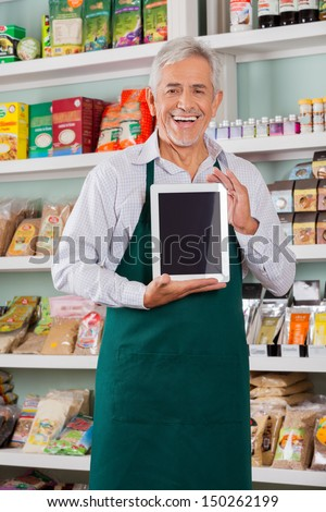 Portrait of happy senior male store owner showing digital tablet in supermarket - stock photo