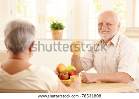 Portrait of happy senior man at breakfast table having tea, sitting with wife.?
