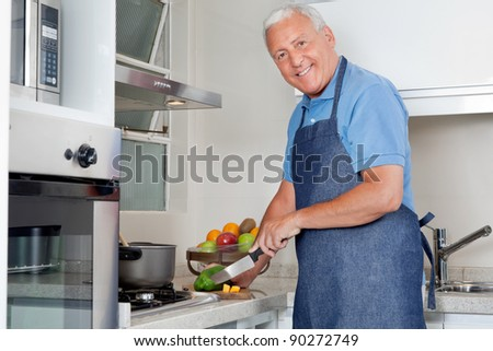 Portrait of happy senior man cutting vegetables at kitchen counter at home - stock photo