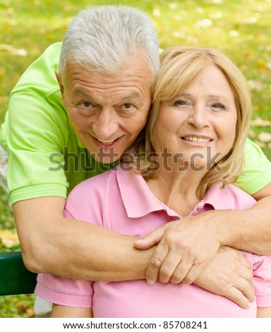 Portrait of happy senior man embracing senior woman outdoors.