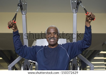 Portrait of happy senior man exercising in gym