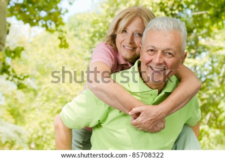 Portrait of happy senior man giving piggyback ride outdoors. - stock photo
