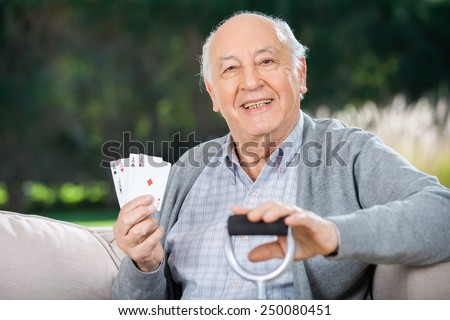 Portrait of happy senior man holding four aces while sitting on couch at nursing home porch - stock photo