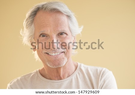 Portrait of happy senior man isolated over beige background