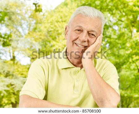 Portrait of happy senior man outdoors. - stock photo