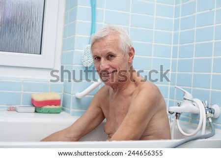 Portrait of happy senior man sitting in bath. - stock photo