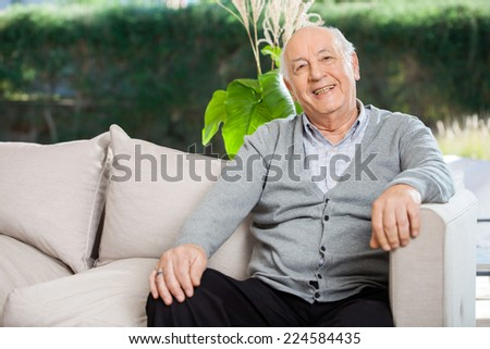 Portrait of happy senior man sitting on couch at nursing home porch - stock photo