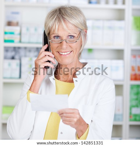 Portrait of happy senior pharmacist using cordless phone while holding prescription paper in pharmacy - stock photo