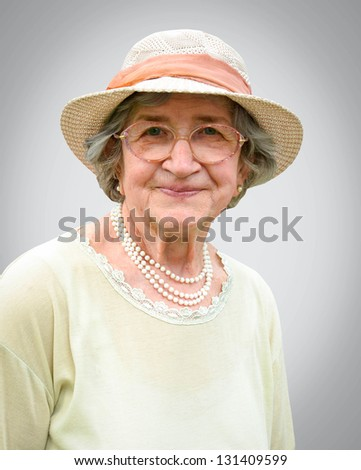 Portrait of happy senior woman against gray background - stock photo