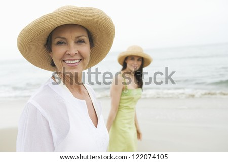 Portrait of happy senior woman and daughter walking at beach - stock photo