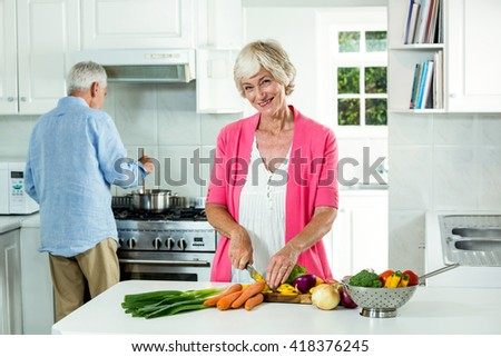 Portrait of happy senior woman cutting vegetables in kitchen - stock photo