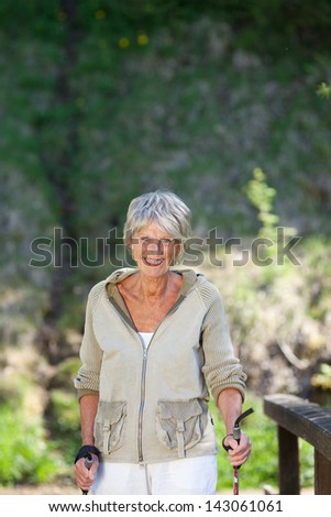 Portrait of happy senior woman hiking in forest - stock photo