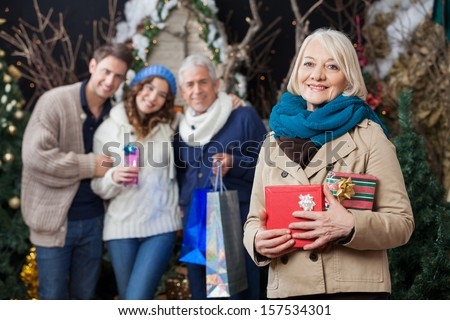 Portrait of happy senior woman holding Christmas presents with family standing in background at store - stock photo