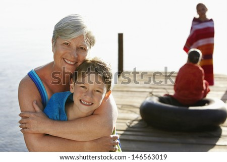 Portrait of happy senior woman hugging grandson on jetty with sisters in background - stock photo