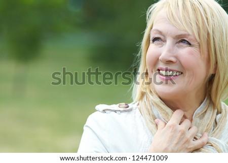 Portrait of happy senior woman in park - stock photo
