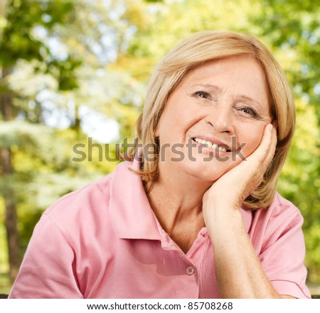 Portrait of happy senior woman in the park. - stock photo