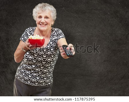 portrait of happy senior woman looking the tv against a grunge wall - stock photo