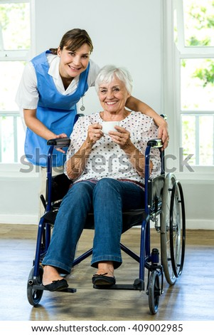 Portrait of happy senior woman on wheelchair with nurse at health club