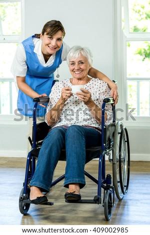 Portrait of happy senior woman on wheelchair with nurse at health club - stock photo