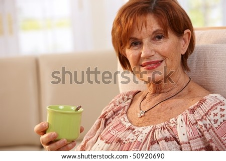 Portrait of happy senior woman sitting in chair at home drinking coffee, smiling.