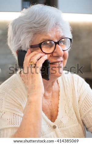 Portrait of happy senior woman talking on smartphone at home. - stock photo