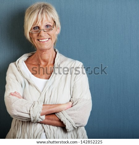 Portrait of happy senior woman with arms crossed standing against blue wall - stock photo