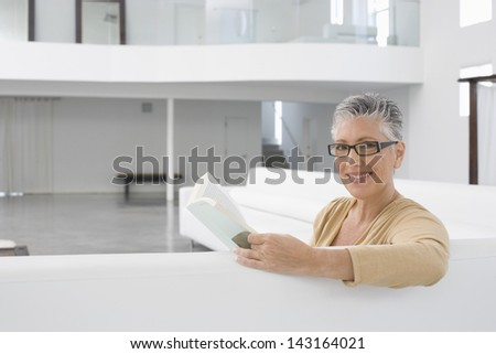 Portrait of happy senior woman with book on sofa at home