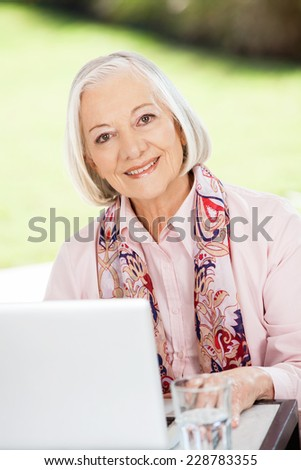 Portrait of happy senior woman with laptop at table on nursing home porch - stock photo
