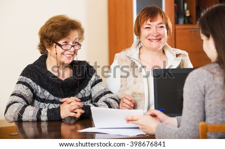 Portrait of happy senior women with papers and agency employee. Focus on left woman - stock photo