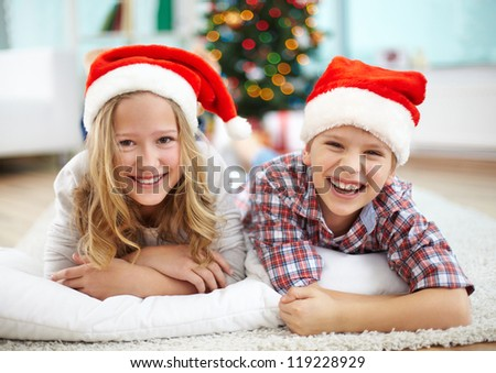 Portrait of happy siblings lying on the floor and looking at camera on Christmas evening - stock photo