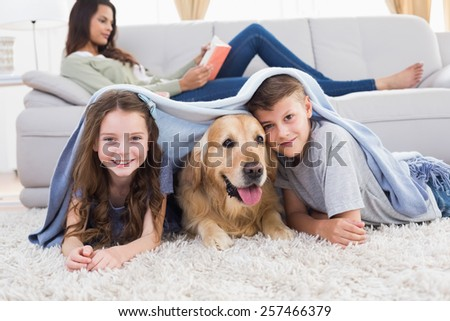 Portrait of happy siblings with dog under blanket at home - stock photo