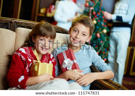 Portrait of happy siblings with giftboxes on Christmas evening - stock photo