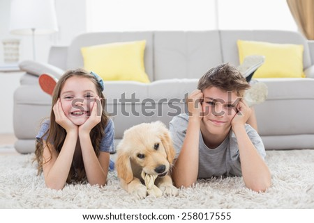 Portrait of happy siblings with puppy lying on rug at home - stock photo