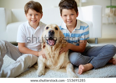 Portrait of happy siblings with their pet looking at camera at home - stock photo