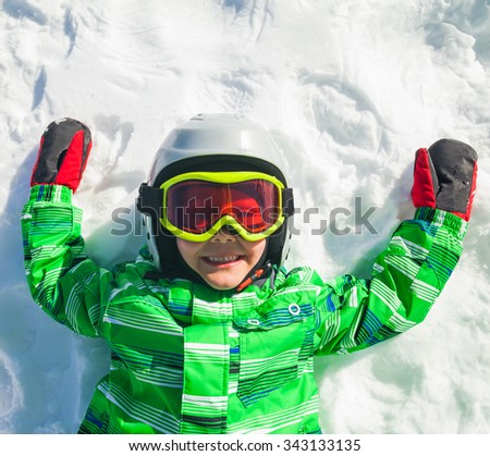 Portrait of happy skier boy lying on the slope in goggles. Winter ski resort. - stock photo