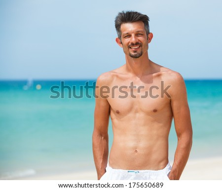 Portrait of happy smiling athletic young man on beach vacation
