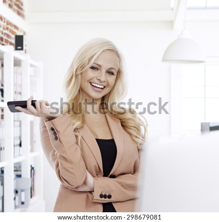 Portrait of happy smiling attractive blonde businesswoman, holding mobile, looking at camera.