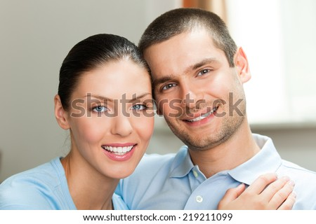 Portrait of happy smiling attractive young couple at home - stock photo