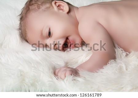 Portrait of happy smiling baby boy on white fur coat background - stock photo