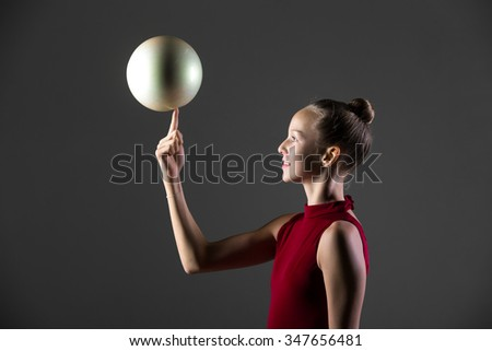 Portrait of happy smiling beautiful cool young fit gymnast athlete woman in sportswear red dress working out, doing art gymnastics exercise, rotating white ball on her finger, studio, dark background - stock photo