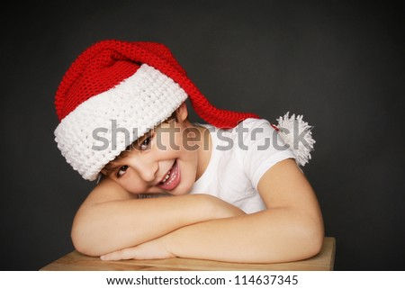 Portrait of happy smiling beautiful little boy in hat of Santa Claus, studio shot - stock photo