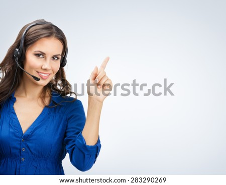 Portrait of happy smiling beautiful young support phone operator showing blank copyspace area for slogan or text - stock photo